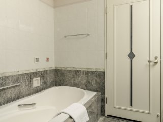 Even the door to the bathroom is stylish, and the lovely stone that lines the walls adds to the classy design.