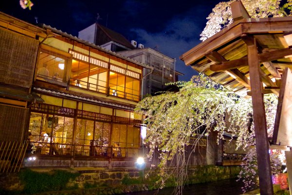 Yellow lights streaming out from riverside restaurants