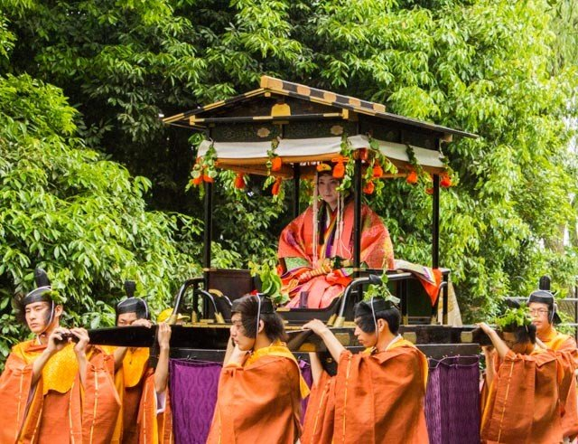 This is this year's Saiō-Dai Lady (斎王代) seated in the Oyoyo Mikoshi and carried by these strong boys. They are approaching the entrance of the Shimogamo shrine