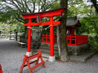 A small red shrine stands on one side of the bridge