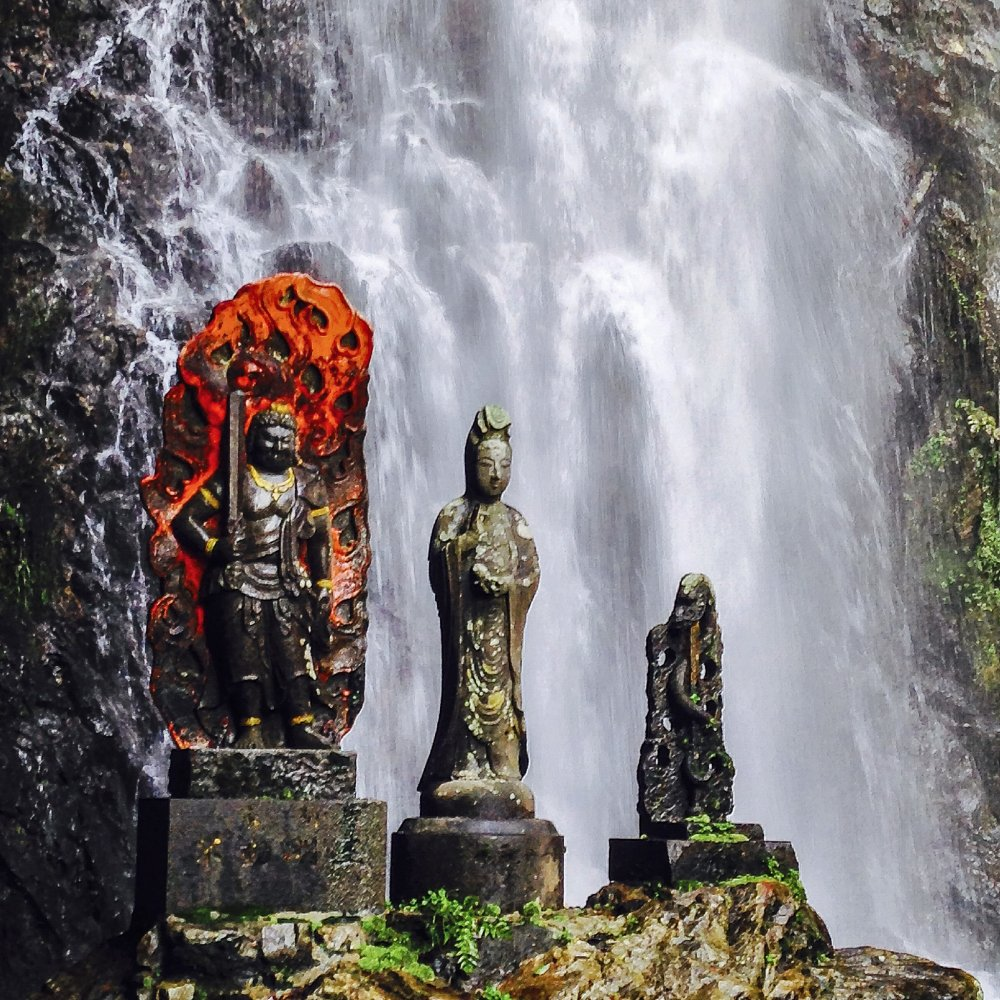 """A few statues stand unwavering in front of the waterfall. The one with the fiery, orange backdrop is called Fudō Myō-ō. His name translates into """"Immovable Wisdom King"""" and the sword he holds is the slayer of ignorance. There are several statues of this deity at this particular site. Can you find them?"""