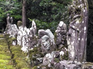 A row of Buddhist statues, centuries old, and weathered over time.