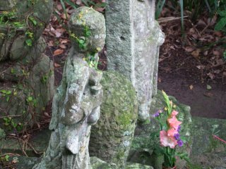 An ancient, lone statue that is well cared for.