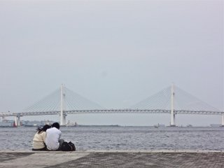 A couple enjoying the view of the Yokohama Bay Bridge.