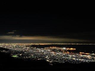วิวยามราตรีจากระเบียงชมวิวบนภูเขามะยะ ซื่งเป็นจุดชมวิวที่ใหญ่ที่สุดของเทือกเขาร็ออกโกะ วิของที่นี่ได้รับเลือกให้เป็นนหนึ่งในสามวิวยามราตรีที่งดงามที่สุดในญี่ปุ่น