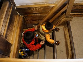 Small children assist one another as they make their way up the challenging staircase