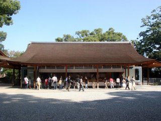 Shinto priests sell ema plaques (wooden plaques onto which people write their prayer)to the public.