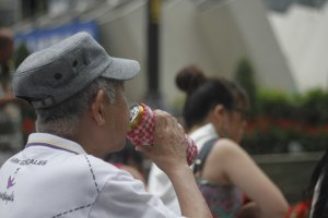 A spectator has a drink while enjoying the show.
