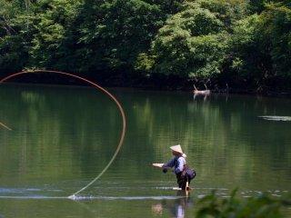 นักตกปลากำลังเหวี่ยงคันเบ็ดลงไปในยุโนะ-โคะ (ทะเลสาบยุโนะ) ในโอะคุ-นิกโกะ