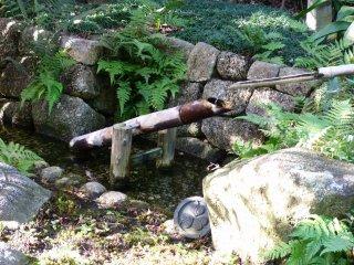 Un shishi-odoshi ( fontaine japonaise) qui se situe le long du lac près de la maison de thé