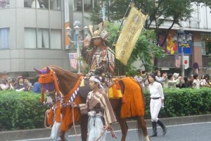 Samurai on horseback parading through the city streets