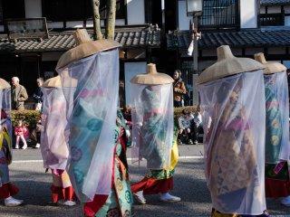 Young women wear traditional Uchikatsugi Veils, originally worn to protect noble identities