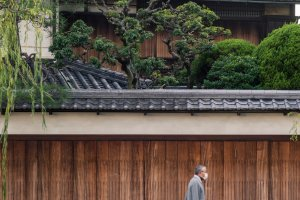An elderly gentleman makes his way by some of the quarter's architecture