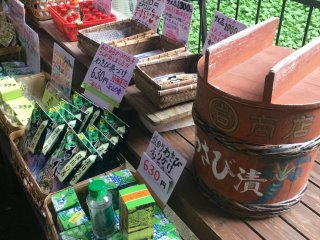 All manner of wasabi products on sale. Bright green wasabi plants in the background.