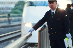 Un conducteur de la compagnie JR regarde les rails alors que le Shinkansen, en provenance de Kyoto et de Shin Osaka, arrive en gare de Tokyo en arrière-plan