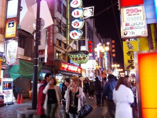 Neon signs turns night into day on the Sidewalks around Dotonbori in Osaka's Naniwa district