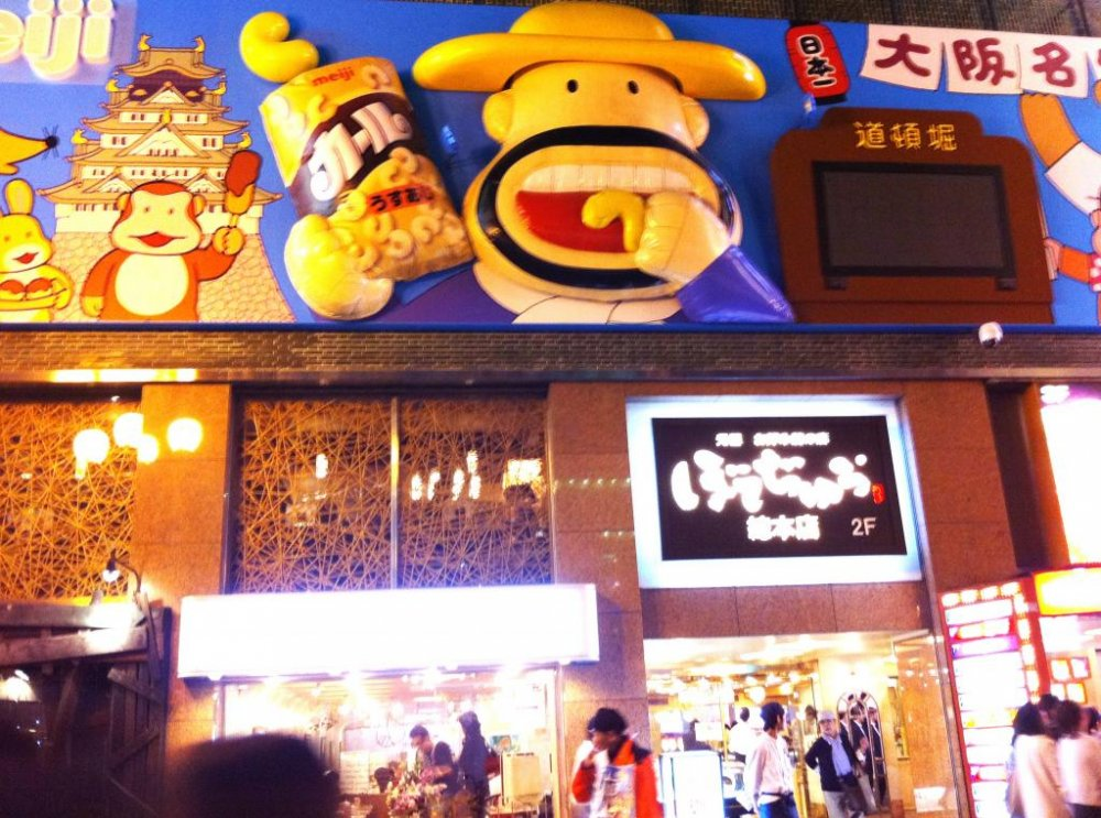 Oversized Cartoon Characters like Popcorn man lure us into a night fantasy that is adult and childlike at the same time at Dotonbori