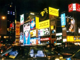 The magic of the night is reflected in the shiny taxicabs on Midosuji dori next to Osaka's heartbeat Dotonbori which is sandwiched between Nanba and Shinsaibashi