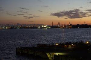 The sun sets behind the port of Nagoya