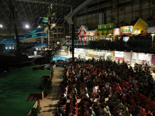 Inside the water park at night, the audience enjoys the hula show.