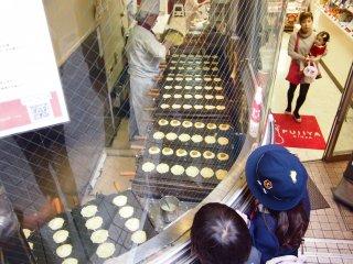 School children looking at the process of baking Pekko-chan Yaki.