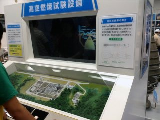A video monitor along with nearby cases exhibit information on engine design and development.