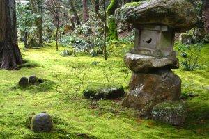 พื้นหญ้าปกคลุมด้วยมอสส์หนา สลับด้วยโคมหินและรูปปั้น สวยแม้ไม่ใช่ฤดูใบไม้เปลี่ยนสี