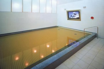 <p>A view of the onsen with the big screen TV to enjoy while you soak in the natural hot waters.</p>
