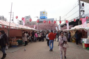 Others enjoy shopping for local foods at several food-stands set up under white tents next to the station.