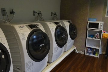 <p>Laundry room with coin-operated washing machine and dryer</p>