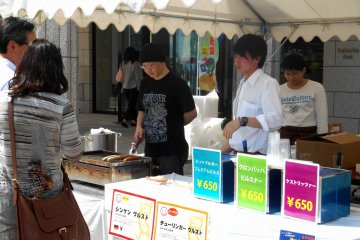 <p>Food stand selling German food in front of the Naruto German House</p>