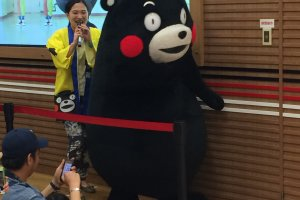 Kumamon makes his way to the stage with his mate. Because he can't speak, his mate interprets in Kumamoto dialect.