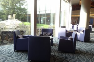 The hotel lobby is arranged in a casual style, with a clear glass wall that looks out to the circular central garden.