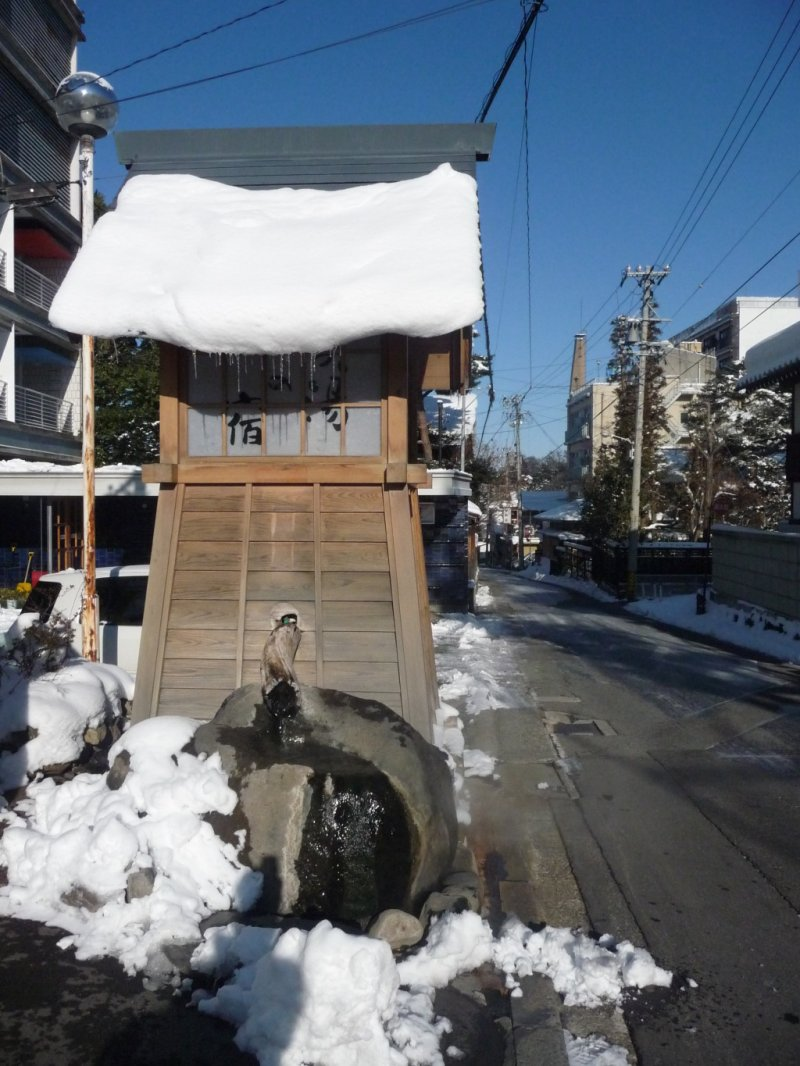 Small fountain flowing with hot spring water at parking lot entrance