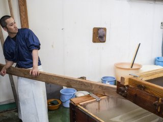 One of many washi workers using a plank to hold up the giant screen used to make the washi.