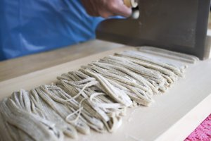 Using a soba knife to slice the sobadough into thin strips