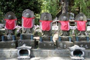 Jizo bosatsu statues line the entrance to the cemetery.