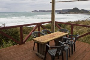 Outdoor seating looks onto the incoming waves
