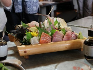 A very well decorated plate of sashimi: thin slices of raw fish, they are delicious with soy sauce.