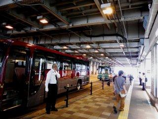 임페리얼 호텔 오사카 (빨간색)와 리가 로열 호텔 (녹색) 셔틀 버스가 사쿠라바시 게이트 버스 정류장에서 멈춰 있다.