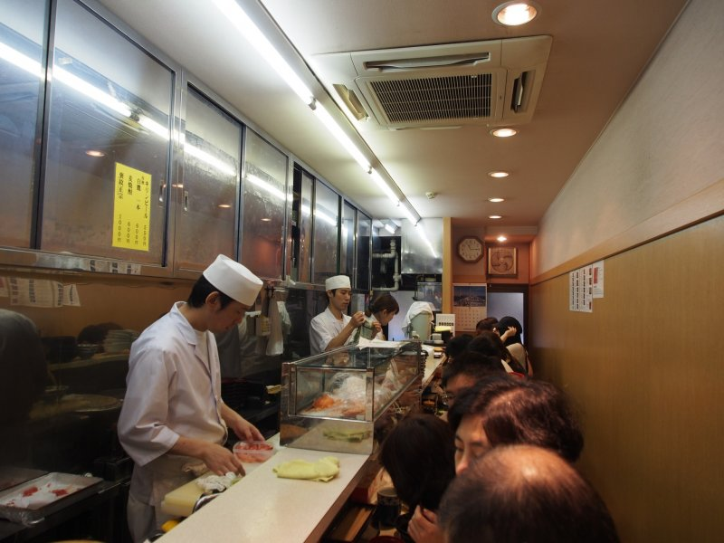 <p>The inside one of the restaurants at the Tsukiji Fish Market &ndash; people are neatly packed in while the chefs efficiently prepare the meals</p>