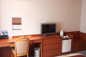 Khu vực bàn làm việc trong phòng ngủ, hoàn chỉnh với tivi, tủ lạnh, tiện nghi pha trà và không gian viết
