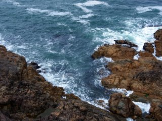 Look down at the swirling ocean around the rocks