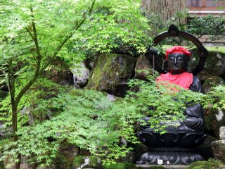 Dark Buddha statue clad in red sits silently in front of the Kisshōkaku Hall