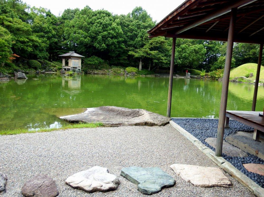 Batu injak, batu bulat, dan kolam tenang di sekitar pemandangan yang hijau