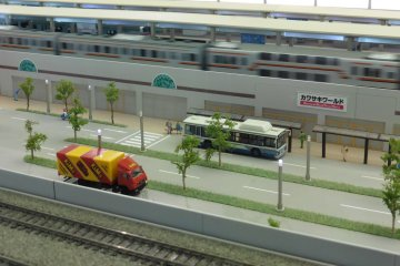 <p>A train passing by Kawasaki World station</p>