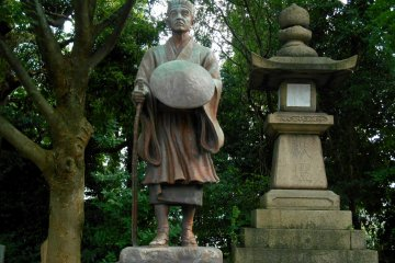 <p>Statue of Matsuo Basho, a famous poet in the Edo Period, standing in the corner of the shrine grounds with a stone lantern and tall trees</p>