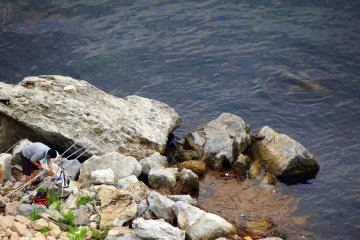 <p>Someone enjoying fishing from the rocky shore</p>