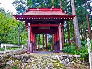 Một cổng màu đỏ sáng rực rỡ nằm bên cạnh một con đường lên núi chạy dọc theo bên cạnh của khu phức hợp này
