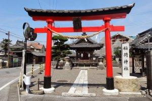 ศาลเจ้าเล็กๆ แห่งหนึ่งมีประตูโทริที่ทางสีแดงสดใส